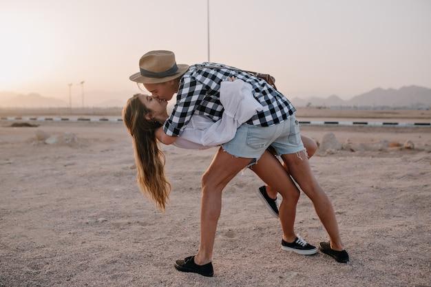 Stijlvolle jongeman in hoed en langharige slanke vrouw dansen op het zand en kussen bij zonsondergang. portret van een schattig omarmen paar in denim shorts, samen tijd doorbrengen op de berg