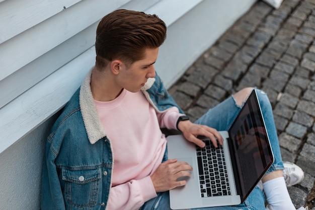 Stijlvolle jongeman in roze sweatshirt in modieuze spijkerbroekkleding werkt op afstand op laptop zittend op stenen tegels in straat. succesvolle blogger werkt, creatief project. werktijd