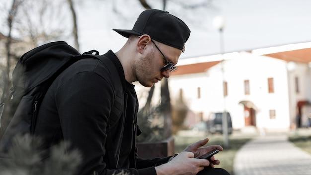 Stijlvolle jongeman in trendy zonnebril in casual kleding in pet met rugzak zit en kijkt naar smartphone buiten in de stad op zonnige dag. knappe man in mode kleding rust op straat.