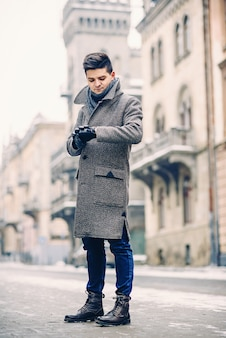 Stijlvolle jongeman in warme grijze jas en lederen handschoenen lopen in de straat. street style.
