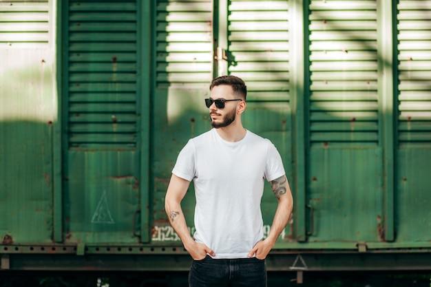 Stijlvolle jongeman met een baard in een wit t-shirt en bril