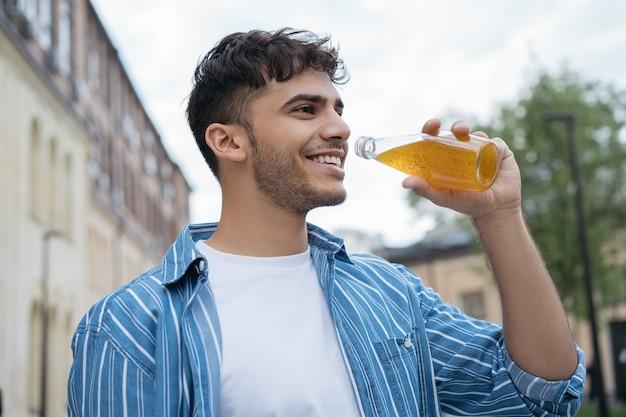 Stijlvolle jongeman met glas met drankjes, wandelen op straat