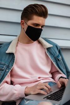 Stijlvolle jongeman met kapsel in zwart beschermend masker in modieuze jeanskleding werkt op afstand op moderne laptop buitenshuis. knappe trendy man beschermt zichzelf tegen covid-19-virus. werk verwijderen.
