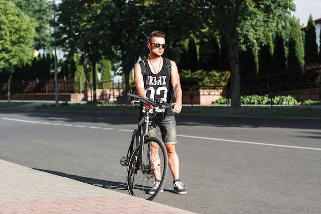 Stijlvolle jongeman permanent op de weg met de fiets