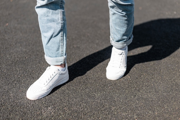 Stijlvolle jongeman staat op een asfaltweg in lederen witte sneakers in stijlvolle blauwe spijkerbroek