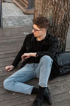 Stijlvolle jongeman toerist in modieuze jeans draagt een bril met leren zwarte rugzak