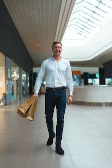 Stijlvolle jongeman wandelen in een winkelcentrum met ecologie vriendelijke boodschappentassen in de hand met goederen en kleding. verkoop, korting uitverkocht concept. seizoensgebonden uitverkocht.