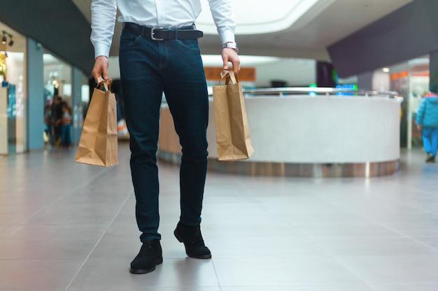 Stijlvolle jongeman wandelen in een winkelcentrum met ecologie vriendelijke boodschappentassen in handen met goederen en kleding. verkoop, korting uitverkocht concept. seizoensgebonden uitverkocht.