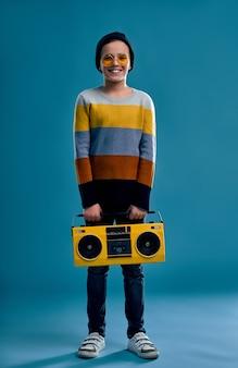 Stijlvolle jongen gekleed in een gestreepte trui, hoed en gele bril houdt een retro bandrecorder geïsoleerd op een blauw.