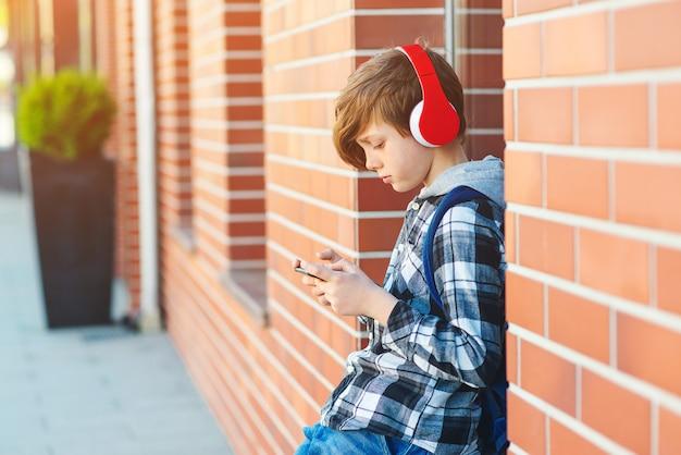 Stijlvolle jongen jongen met koptelefoon met behulp van telefoon op straat in de stad. de jonge jongen speelt online spel bij smartphone. preteenjongen luistert naar de muziek op slimme telefoon
