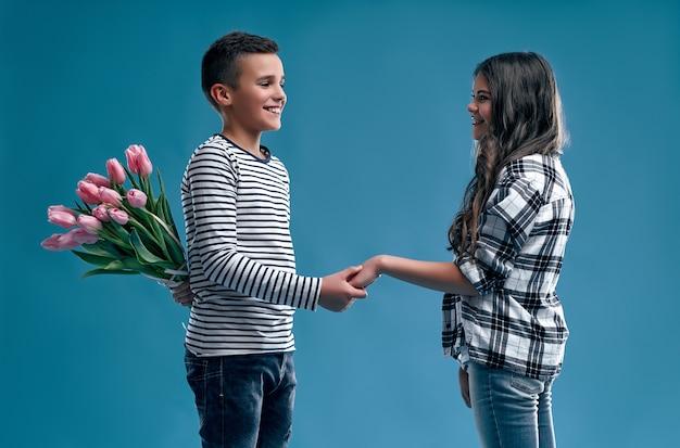 Stijlvolle jongen verstopte achter zijn rug een boeket tulpenbloemen die hij wil geven aan een schattig meisje geïsoleerd op een blauwe achtergrond