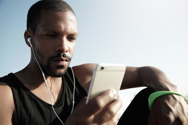 Stijlvolle jongere zittend op de trap bij het water en luisteren naar muziek. eenzame afro-amerikaanse man in zwarte mouwloos met groene fitness tracker genieten van muziek en sms'en op het apparaat.