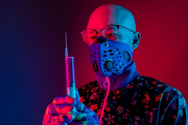 Stijlvolle kale man met gasmasker en bril en spuit met vaccin te houden