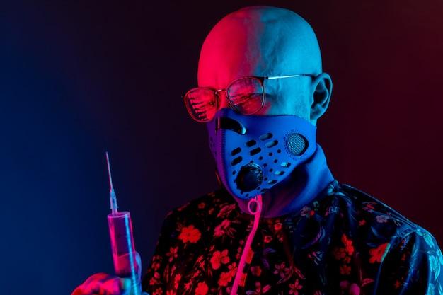 Stijlvolle kale man met medische masker met bril en spuit met vaccin te houden
