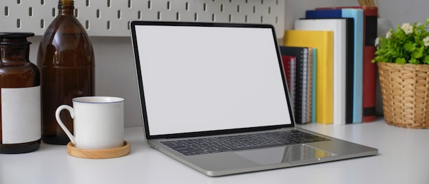 Stijlvolle kantoor aan huis bureau met leeg scherm laptop, boeken, beker en decoraties op witte tafel