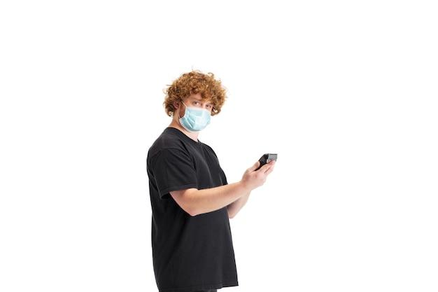 Stijlvolle kapper in beschermend gezichtsmasker geïsoleerd op witte studio muur