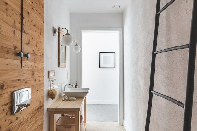 Stijlvolle keramische spoelbak op trendy houten consoletafel in kleine elegante badkamer