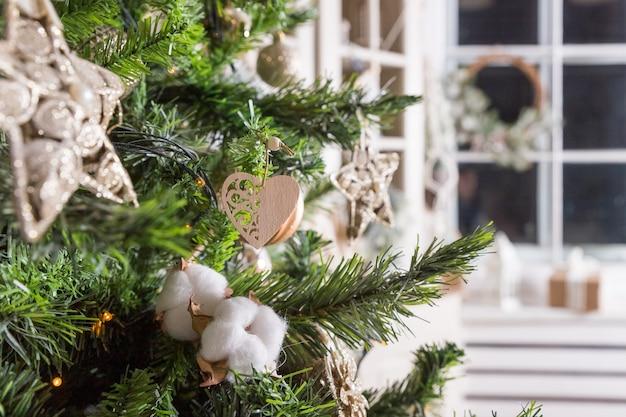 Stijlvolle kerstboom met houten hart, engel, dennen, dennentakken en katoen. droge katoenen bloemen, versierde kerstboom pijnboom