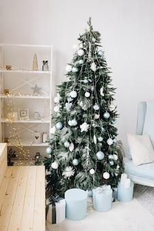 Stijlvolle kerstboom omgeven door ingepakte cadeautjes