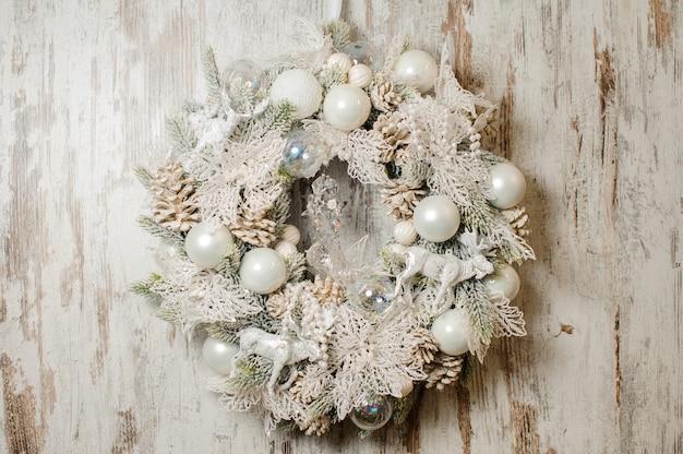Stijlvolle kerstkrans gemaakt van dennenboom en gedecoreerd in witte tinten