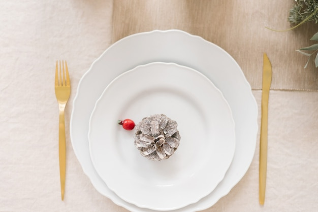 Stijlvolle kersttafel met twee witte borden die op elkaar zijn geplaatst