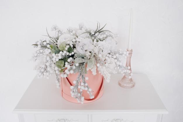 Stijlvolle kerstversiering, boeket rozen naast een sierkaars