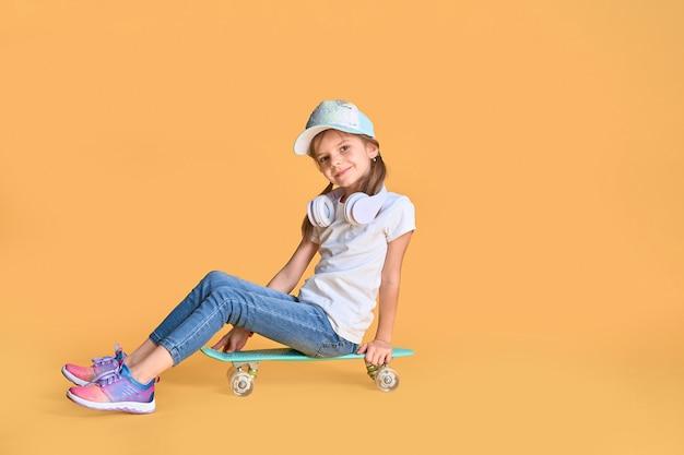 Stijlvolle klein meisje kind meisje in casual met skateboard over geel.