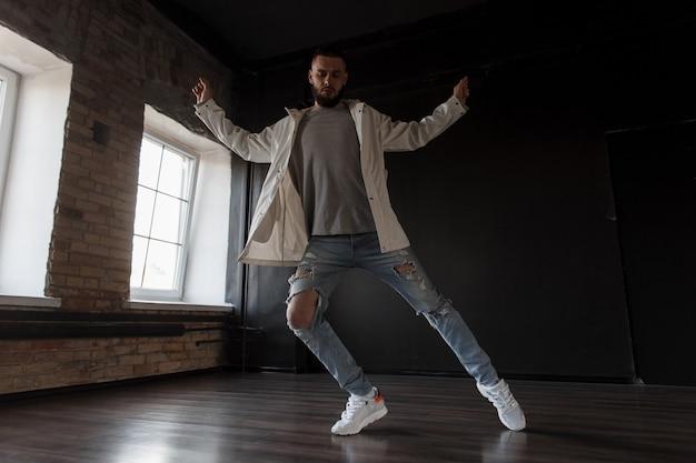 Stijlvolle knappe aantrekkelijke jongeman danser in trendy jasje met mode gescheurde spijkerbroek en witte sneakers dansen in dansstudio op donkere muur. dans levensstijl