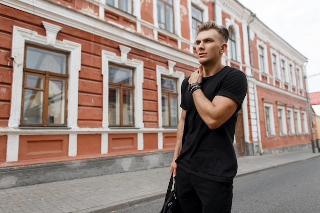 Stijlvolle knappe jonge amerikaanse man met kapsel in zwarte kleding met een zwarte tas loopt in de stad op straat