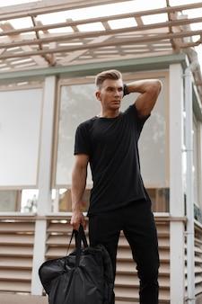 Stijlvolle knappe jonge hipster man met kapsel in zwarte kleding met een zwarte tas op straat in de buurt van een houten gebouw