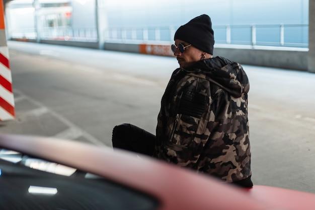 Stijlvolle knappe jonge hipster man met zonnebril en een zwarte hoed in een modieuze winter militaire jas zit op een rode auto in de stad