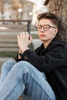 Stijlvolle knappe jonge kerel met een kapsel in modieuze dameskleding met een jas en bril zit in de stad