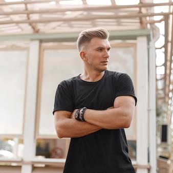 Stijlvolle knappe jonge mannequin man met kapsel in zwart t-shirt staat in de buurt van een houten gebouw op straat