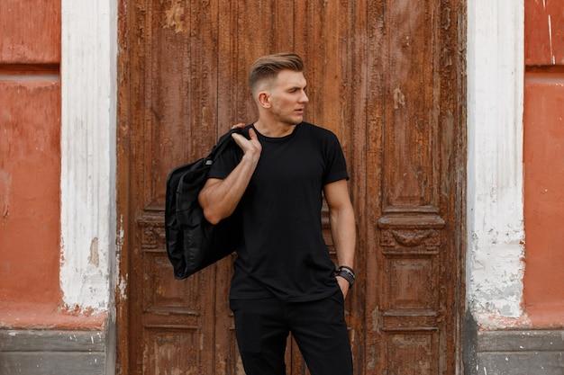 Stijlvolle knappe jonge modelkerel met een kapsel in zwarte kleding met een zak die zich dichtbij een houten uitstekende deur bevindt