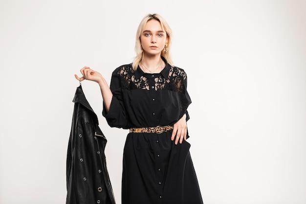 Stijlvolle knappe jonge vrouw in modieuze zwarte jurk met kant met vintage luipaardriem houdt trendy leren jas in de hand. mooi mooi elegant meisje model poseert in de buurt van witte muur.