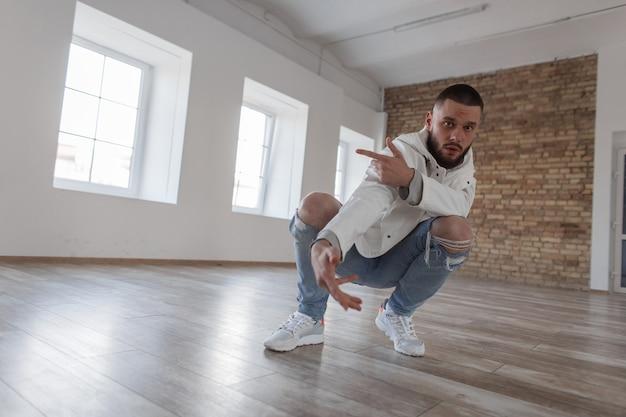 Stijlvolle knappe jongeman danser in trendy jasje en mode gescheurde spijkerbroek met sneakers poseren en zitten in een studio met daglicht