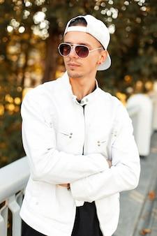 Stijlvolle knappe jongeman in zonnebril in witte modieuze kleding in een zonnige herfstdag