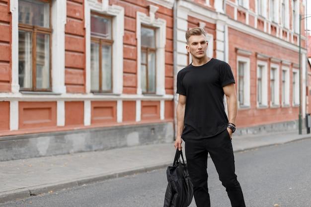 Stijlvolle knappe jongeman in zwarte modieuze mockupkleren met een zwarte tas loopt in de stad