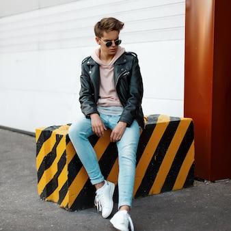 Stijlvolle knappe jongeman in zwarte zonnebril in modieuze kleding met een kapsel, zittend op een gestreepte zwart-gele betonnen plaat in de buitenlucht in de buurt van de witte metalen poorten. amerikaanse moderne kerel