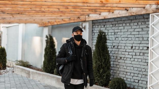 Stijlvolle knappe jongeman met een beschermend medisch masker in een modieuze zwarte jas, hoodie en pet met een rugzak loopt door de stad