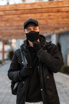 Stijlvolle knappe jongeman met een medisch masker en een zwarte pet in een zwarte modieuze jas, een hoodie met een rugzak loopt door de stad.