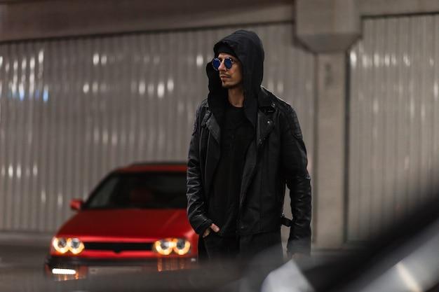 Stijlvolle knappe jongeman met zonnebril in een modieuze zwarte uitloper met een leren jas en een hoodie loopt 's nachts in de buurt van een rode auto op straat