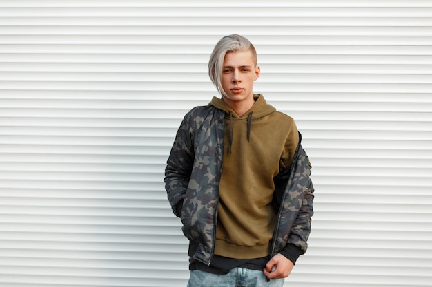 Stijlvolle knappe man in een trendy militair jasje met hoodie poseren in de buurt van witte metalen muur