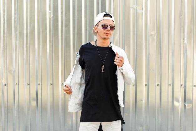 Stijlvolle knappe man in een zwart t-shirt met een wit jasje in fashion zonnebril in de buurt van de metalen wand
