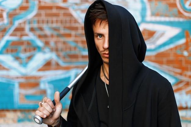Stijlvolle knappe man in zwarte kleding met een kap staande in de buurt van een bakstenen muur met graffiti