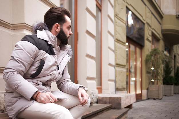 Stijlvolle knappe man met een baard in een winterjas met bont poseren buitenshuis.