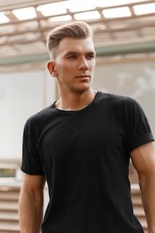 Stijlvolle knappe model man met kapsel in zwart t-shirt op straat in de stad