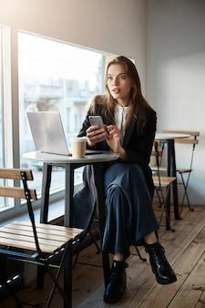 Stijlvolle knappe moderne vrouw in een lokaal café zit in de buurt van raam, koffie drinken terwijl u werkt in een laptop, met smartphone om de baas te bellen