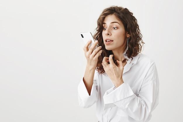 Stijlvolle knappe vrouw die make-up controleert in de camera van haar smartphone