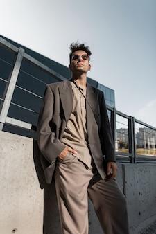 Stijlvolle knappe zakenman man model in trendy grijs pak met zonnebril in de stad. stedelijke mannelijke stijl